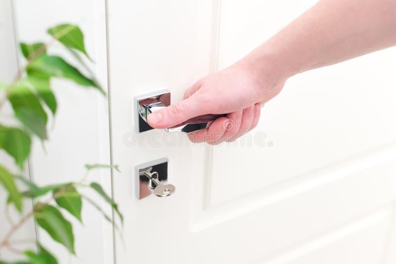 有现代镀铬物门把手的男性手 公寓的内部的特写镜头元素 库存图片