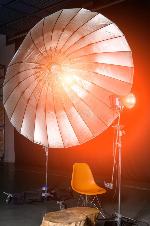 有现代内部和照明设备的空的照片演播室 演播室射击的准备:空的椅子和演播室照明设备 免版税库存照片