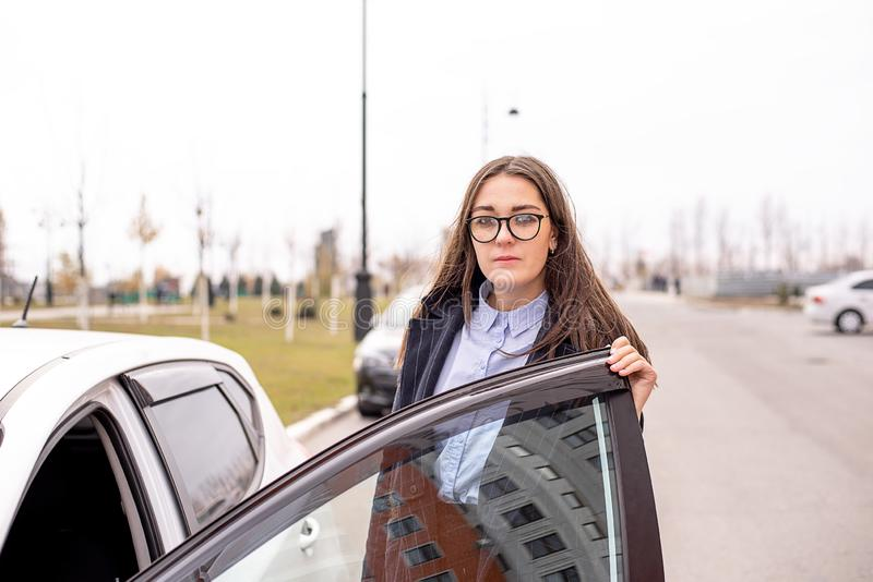 有玻璃、一件蓝色衬衣和外套的一名妇女在有开放的门的汽车旁边站立 库存图片