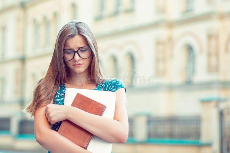 有玻璃书的学生哀伤的妇女,在手中看下来在学院前面的膝上型计算机 免版税库存图片