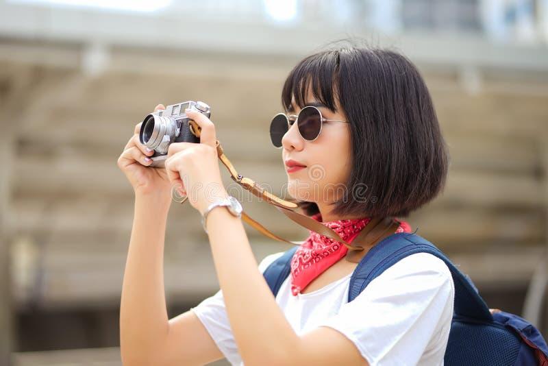 有玻璃和帽子的行家美丽的年轻亚裔妇女拍照片使用减速火箭的胶卷相机在城市晚上 免版税库存图片