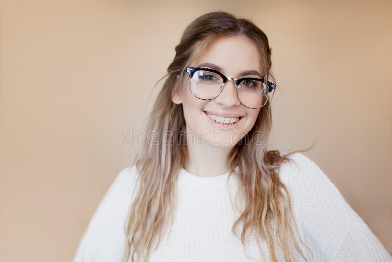 有玻璃和括号的愉快和美丽的女孩 微笑的妇女年轻人 免版税库存图片