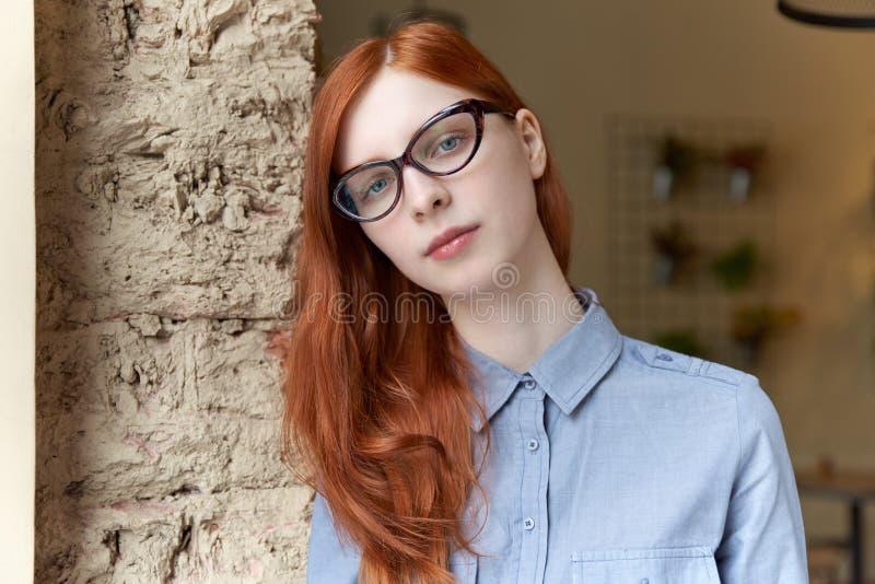 有玻璃和蓝色衬衣stu的年轻可爱的红发女孩 免版税库存照片