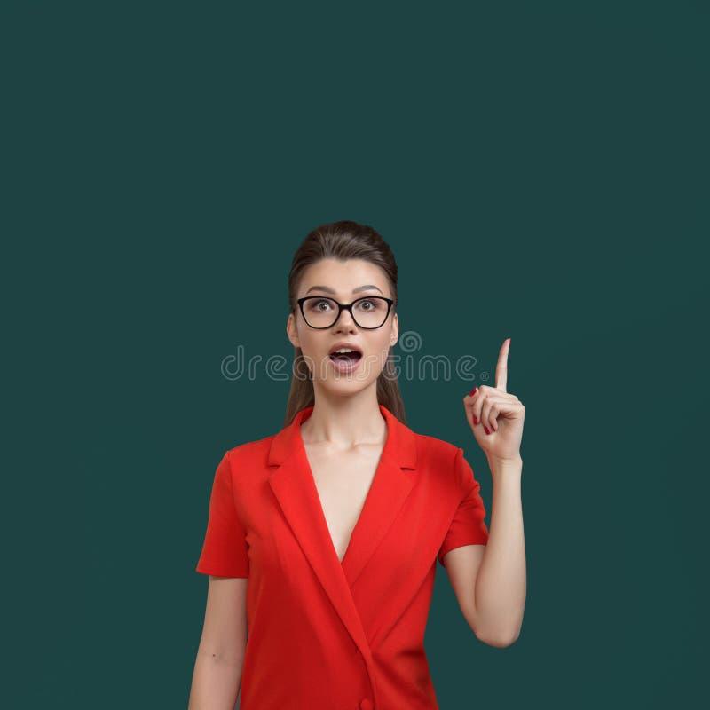 有玻璃点手指的年轻女人 时髦的明亮的衣裳 办公室经理 免版税库存照片