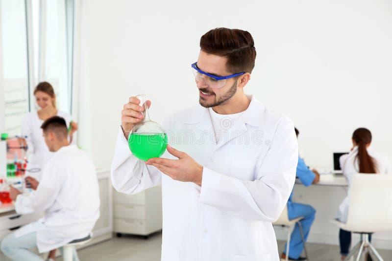 有玻璃烧瓶工作的医科学生在现代科学 库存图片