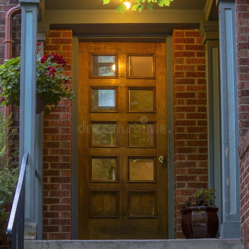 有玻璃的砖房子paned棕色木前门 库存图片