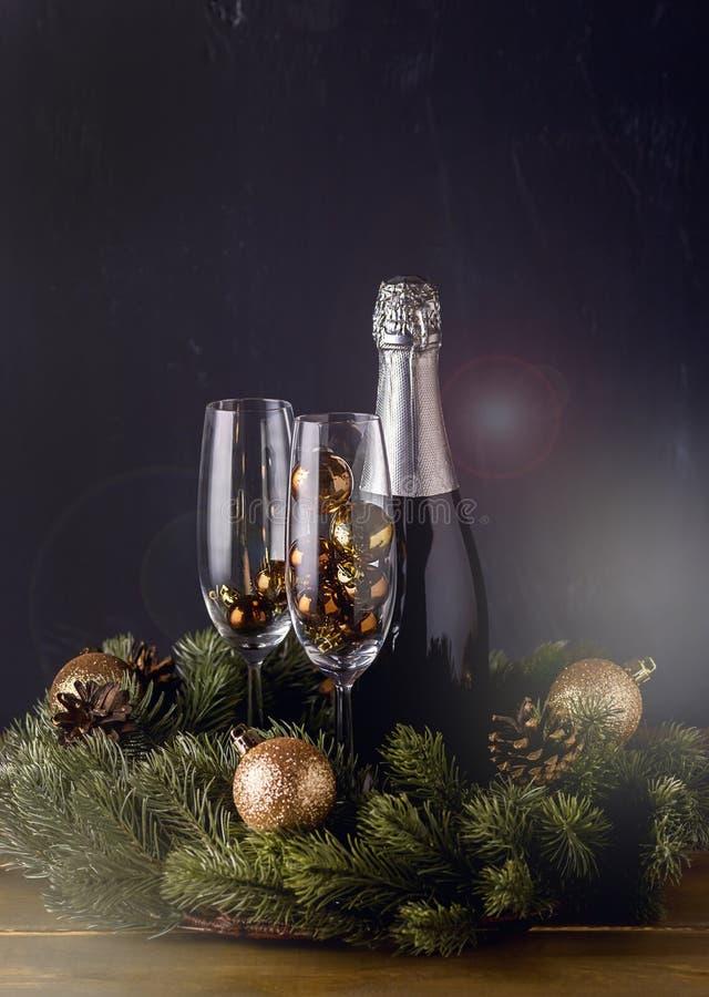 有玻璃的香宾瓶与装饰木背景圣诞节新年假日卡片新年背景垂直 免版税库存图片