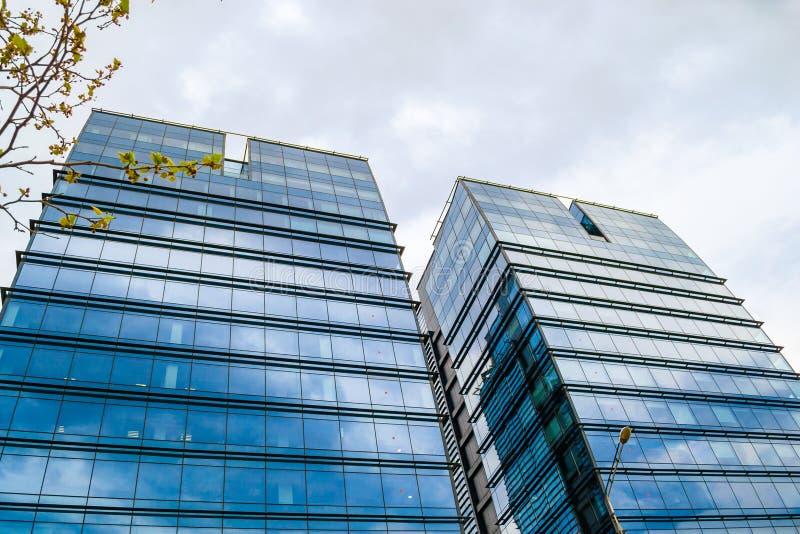 有玻璃窗的双摩天大楼在与反射在大厦的外部的云彩的一风暴日蓝色 免版税图库摄影