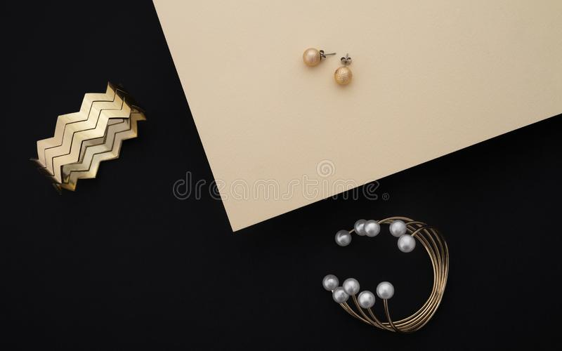 有珍珠和之字形形状袖口的金黄镯子和对在黑和米黄纸背景的耳环 免版税库存照片