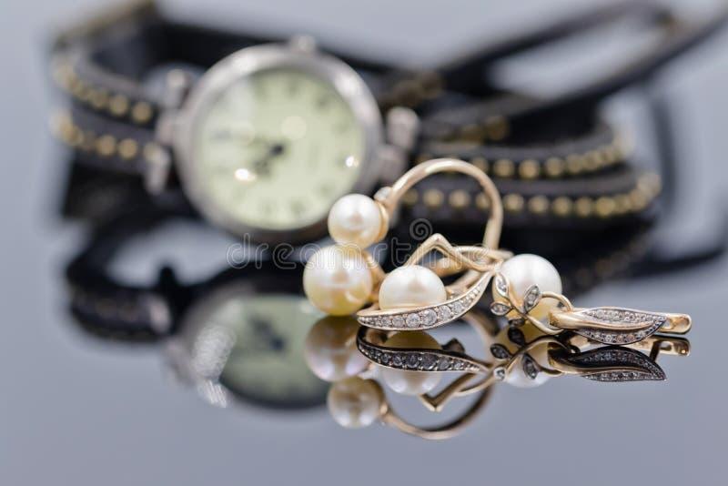 有珍珠的金耳环在手表背景  免版税库存图片