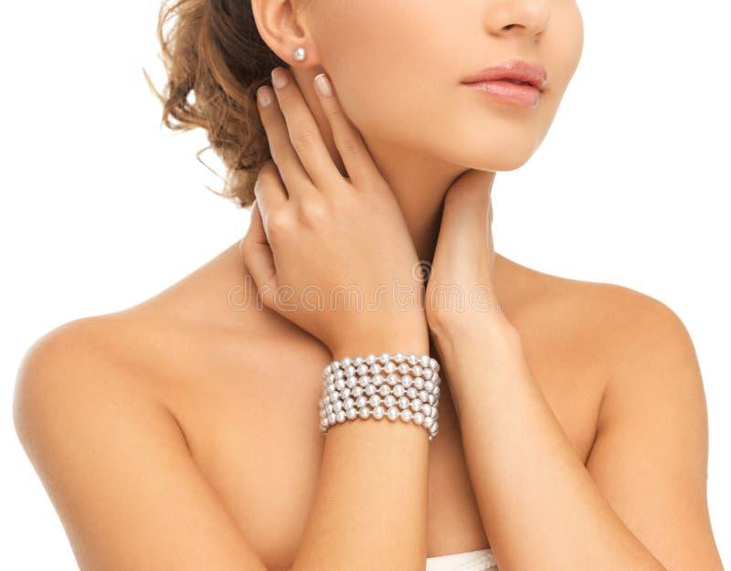 有珍珠耳环和镯子的美丽的妇女 库存照片