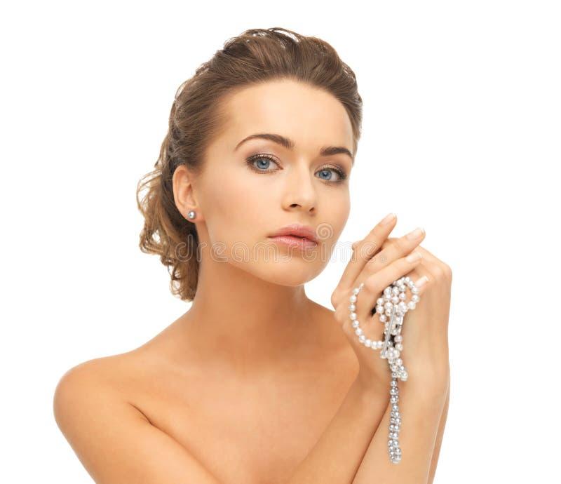 有珍珠耳环和项链的妇女 免版税库存照片