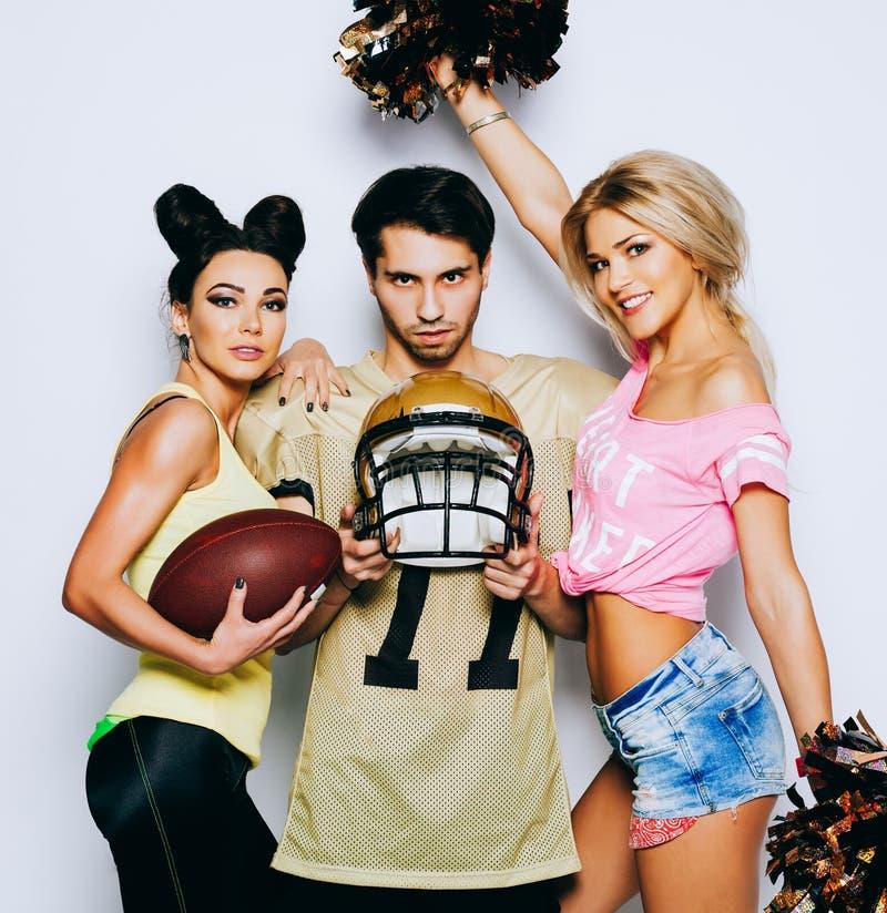 有球、页喷粉器和摆在与盔甲的四分卫美国橄榄球运动员的两个迷人的啦啦队员女孩 免版税图库摄影