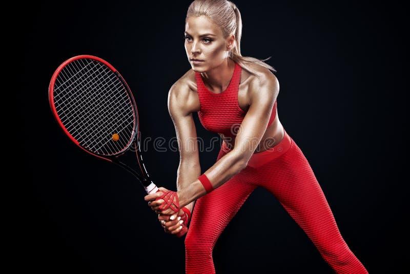 有球拍的美丽的白肤金发的体育女子网球员在红色服装 免版税库存照片