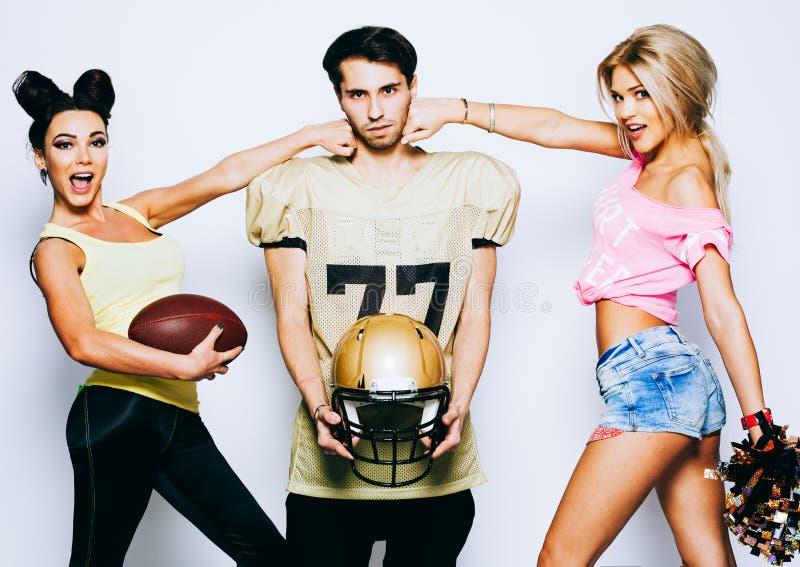 有球的两位迷人的啦啦队员在有盔甲的一名四分卫美国橄榄球运动员触击 免版税库存图片