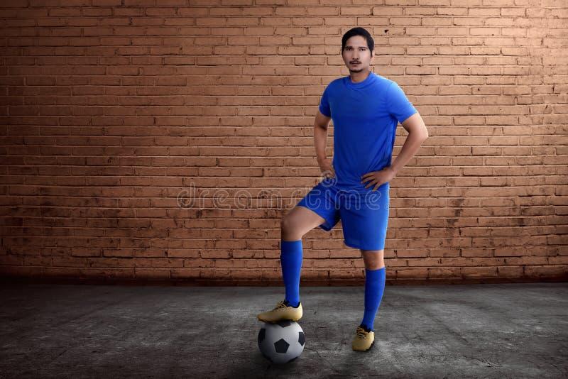 有球的年轻亚裔足球运动员在他的脚 免版税图库摄影