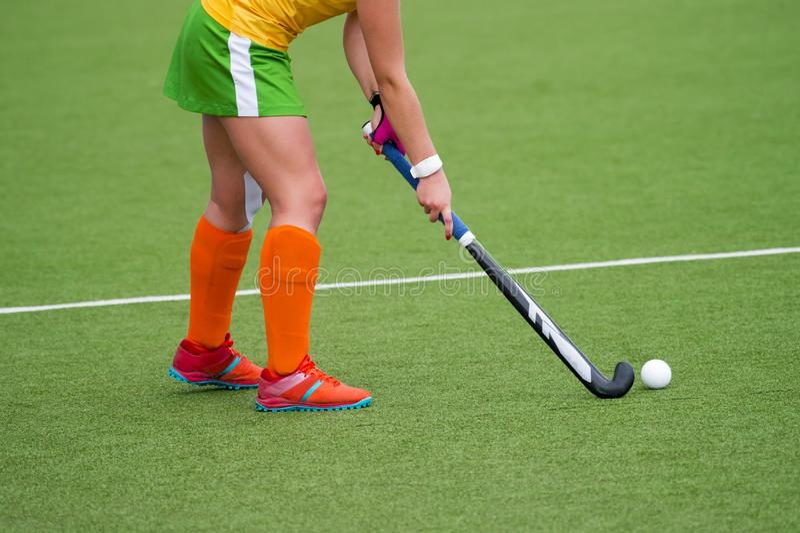 有球的年轻曲棍球运动员妇女在攻击运动场曲棍球赛 库存图片