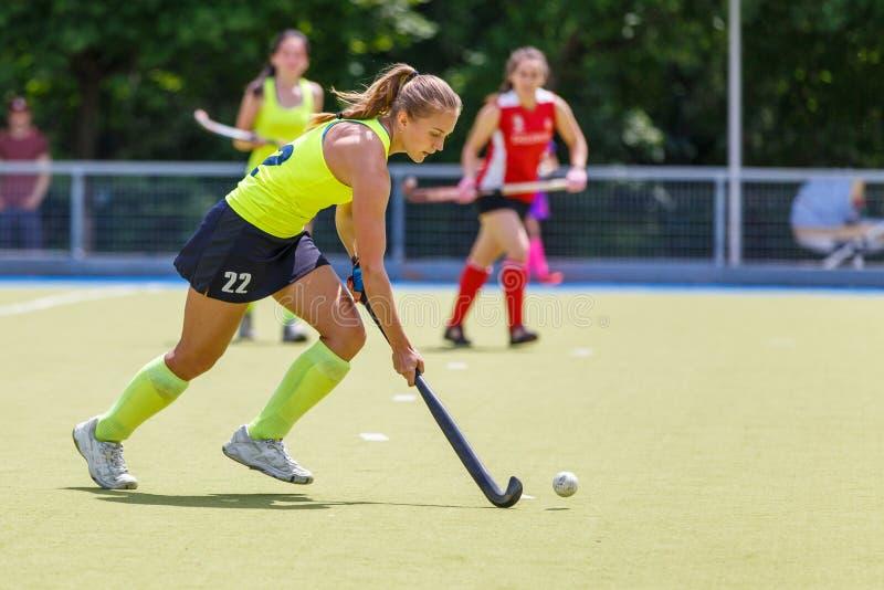 有球的年轻曲棍球运动员妇女在攻击 免版税库存照片