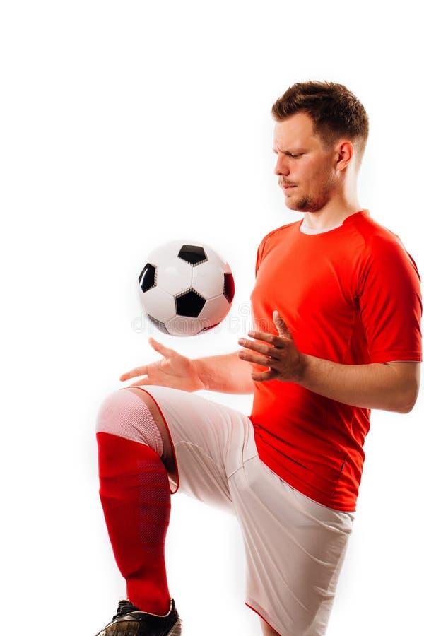 有球的年轻足球运动员在黑背景在演播室 免版税图库摄影