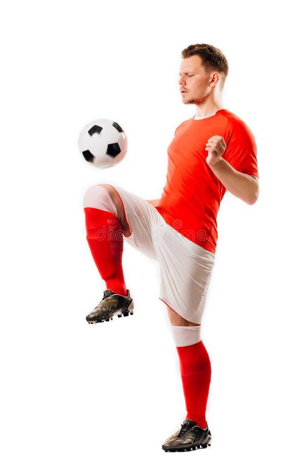 有球的年轻足球运动员在黑背景在演播室 免版税库存照片