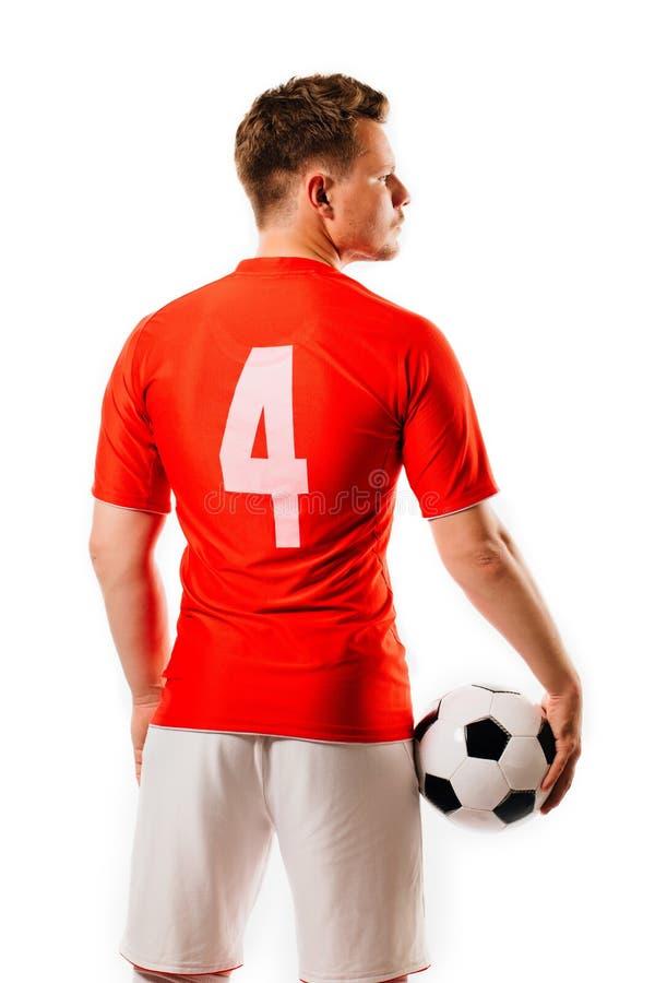有球的年轻足球运动员在黑背景在演播室 库存照片