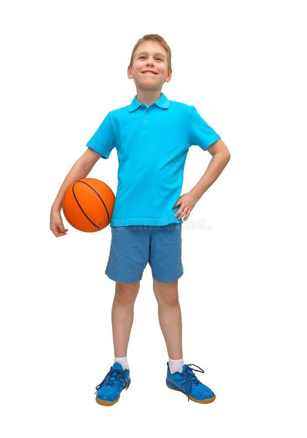 有球的微笑的蓝球运动员男孩 库存照片