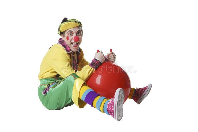 有球的滑稽的小丑在空白背景查出的工作室 免版税图库摄影