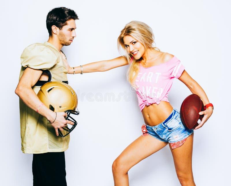 有球的美丽的白肤金发的女孩啦啦队员攻击一位四分卫 橄榄球制服的一个球员有盔甲的 库存照片