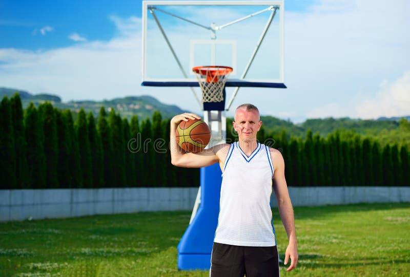 有球的蓝球运动员在户外篮子法院 免版税库存图片