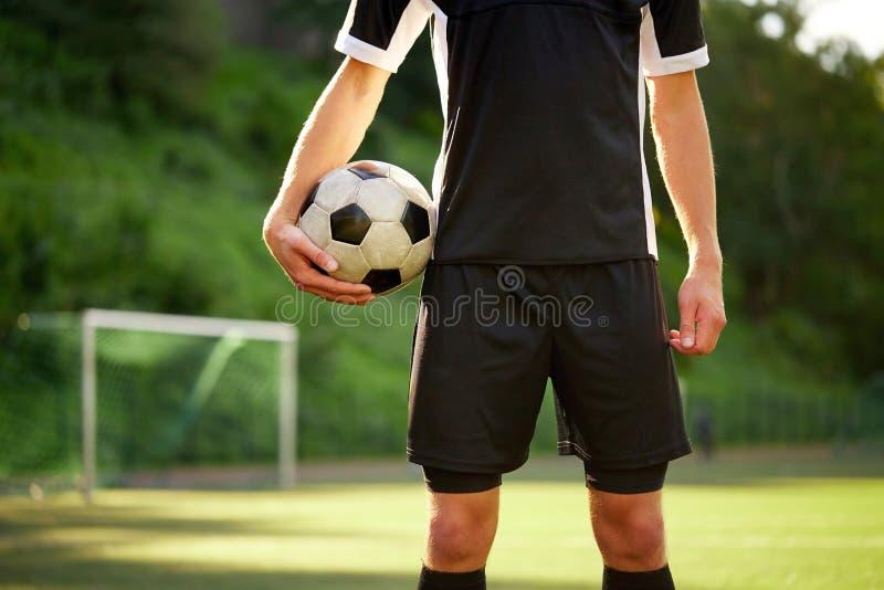 有球的足球运动员在橄榄球场 免版税图库摄影