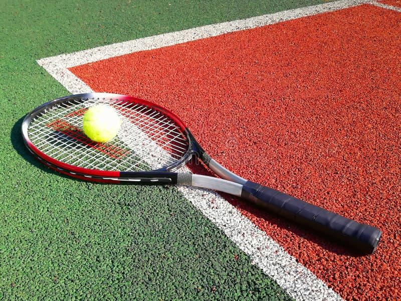 有球谎言的网球拍在一个开放网球场 免版税库存图片