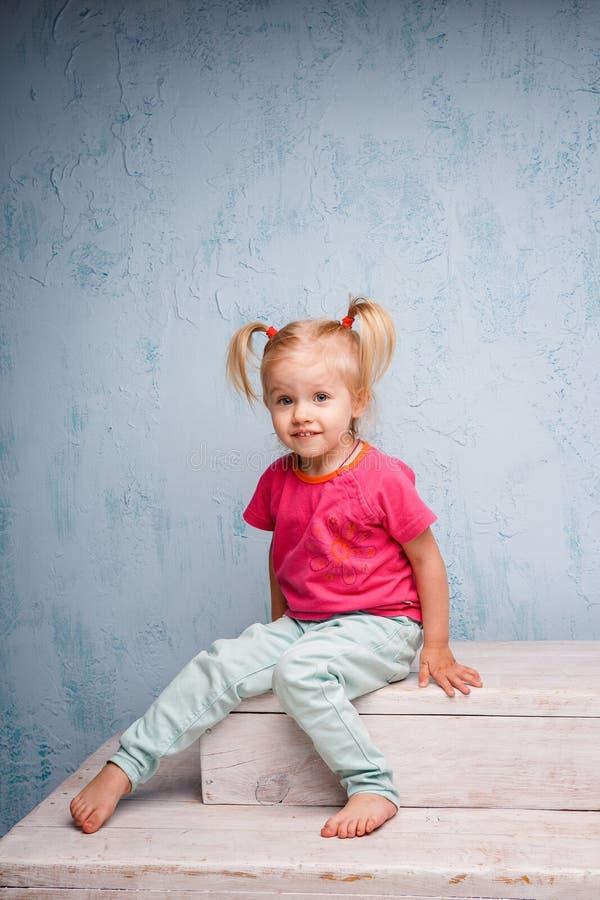 有理发两马尾辫的小滑稽的蓝眼睛的女孩儿童金发碧眼的女人在她的头坐在背景的闲话老 免版税库存图片