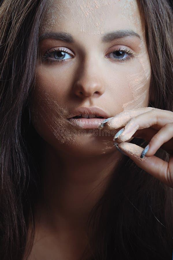 有理想的皮肤的新美丽的妇女在应用奶油和粉末的本质构成 免版税库存照片