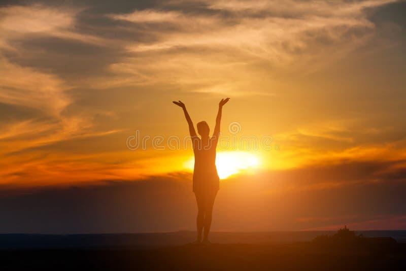 有瑜伽姿势的妇女在日落的山 免版税库存图片
