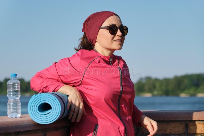 有瑜伽席子和瓶的中年体育妇女水 免版税库存照片