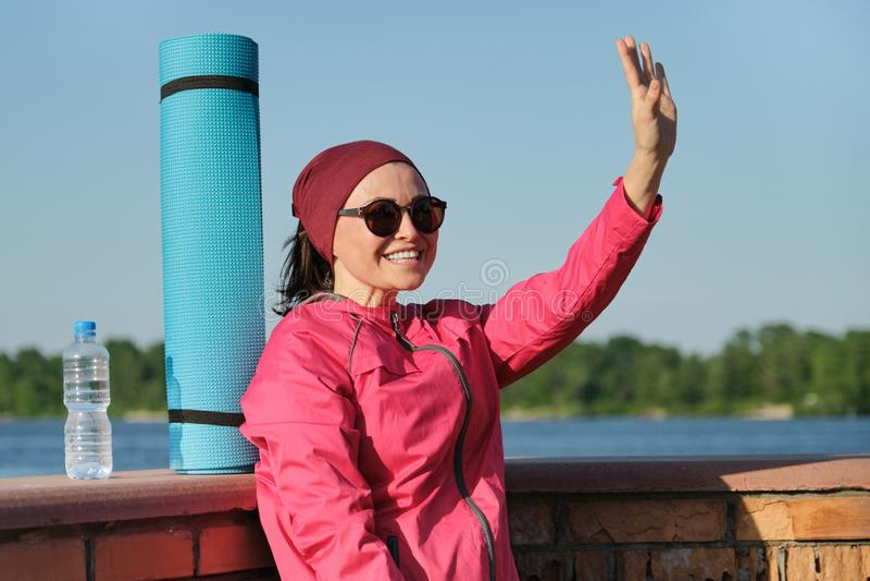 有瑜伽席子和瓶的中年体育妇女水 库存照片