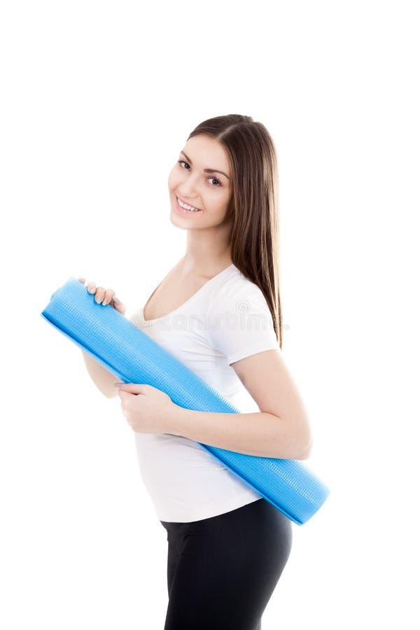 有瑜伽席子的微笑的运动的女孩 免版税库存图片