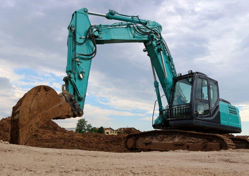 有瓢的大挖掘机在土,反对灰色多云天空 免版税库存图片