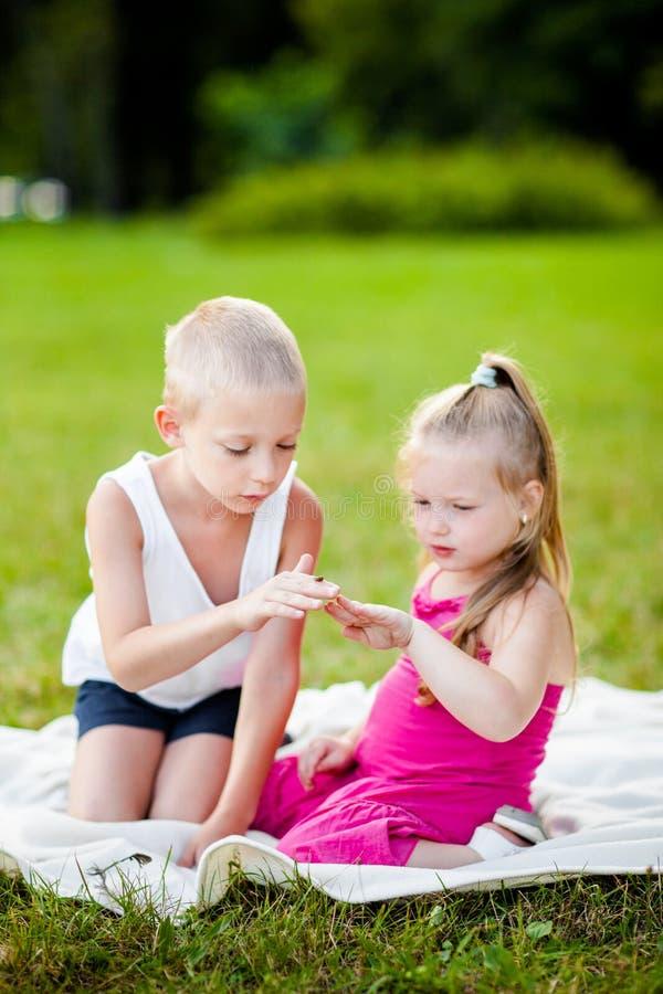 有瓢虫的小男孩和女孩在公园 免版税库存图片