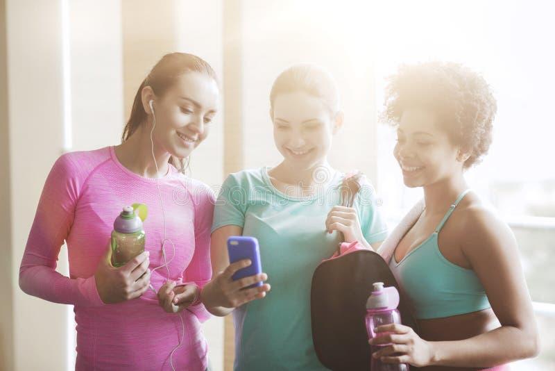 有瓶和智能手机的愉快的妇女在健身房 免版税图库摄影