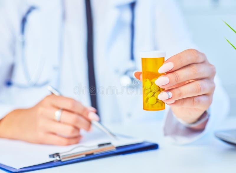 有瓶子的女性医学医生药片和给患者写处方在工作台 万能药和生活救球 免版税库存图片