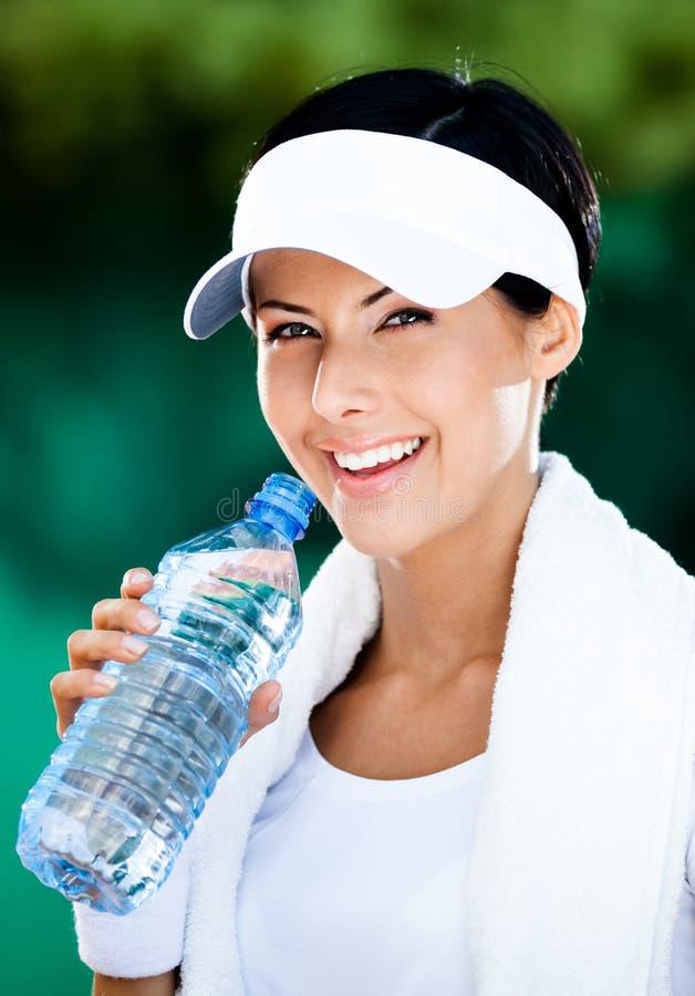 有瓶的兴高采烈的运动的妇女水 库存图片