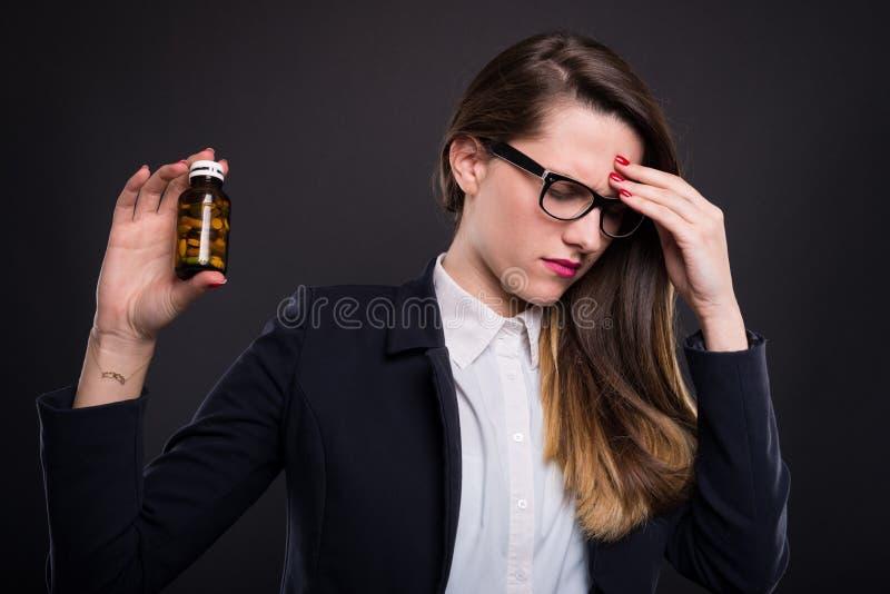 有瓶的十分厌倦女实业家药片 免版税库存照片