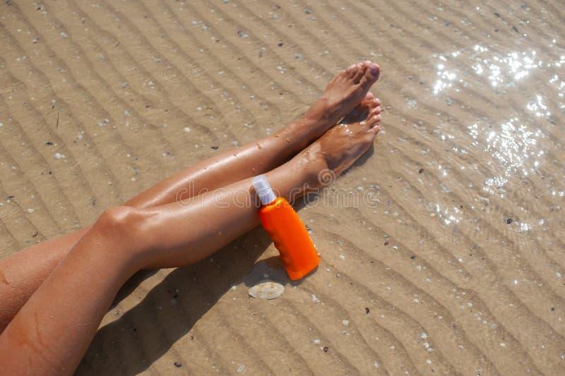 有瓶的妇女在她的手附近的遮光剂 Skincare Sunblock太阳她光滑的被晒黑的腿的保护奶油 Suncream和 免版税库存图片