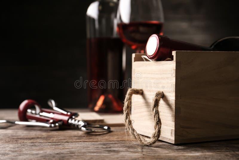 有瓶的开放木板箱酒和拔塞螺旋在桌上 库存照片