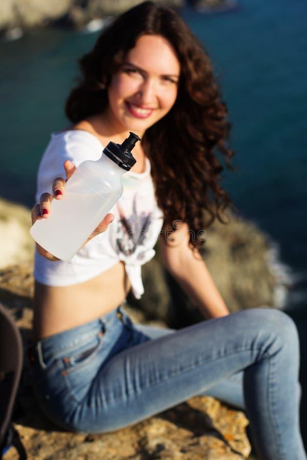 有瓶的愉快的女孩背包徒步旅行者水 免版税库存照片