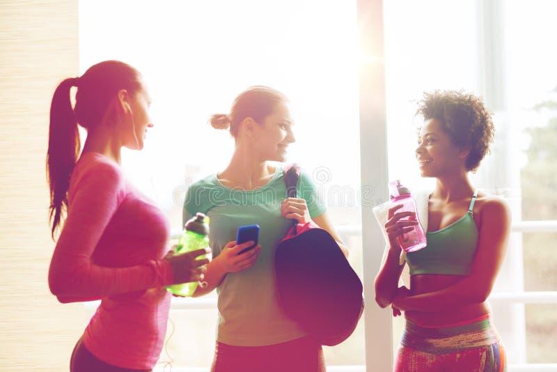 有瓶的愉快的妇女在健身房的水 免版税库存照片