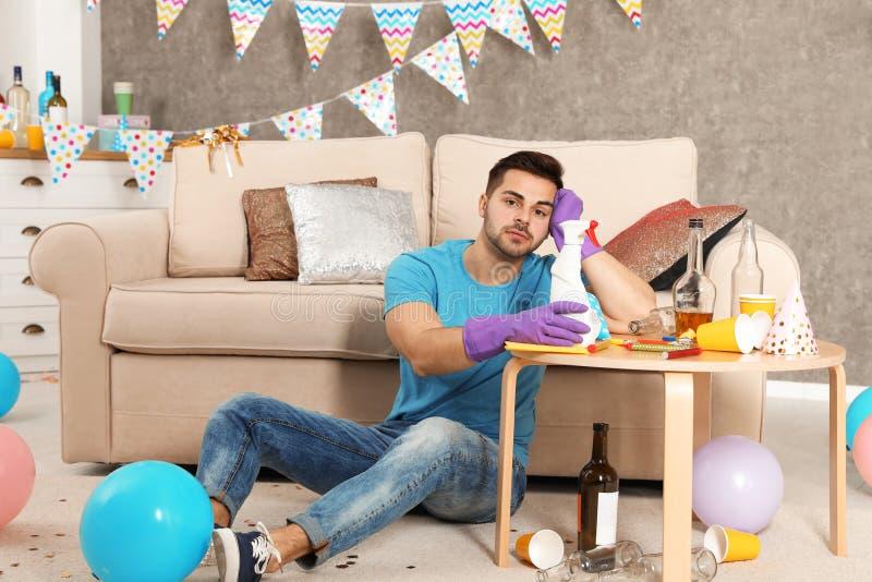 有瓶的疲乏的年轻人洗涤剂在杂乱屋子里 库存照片