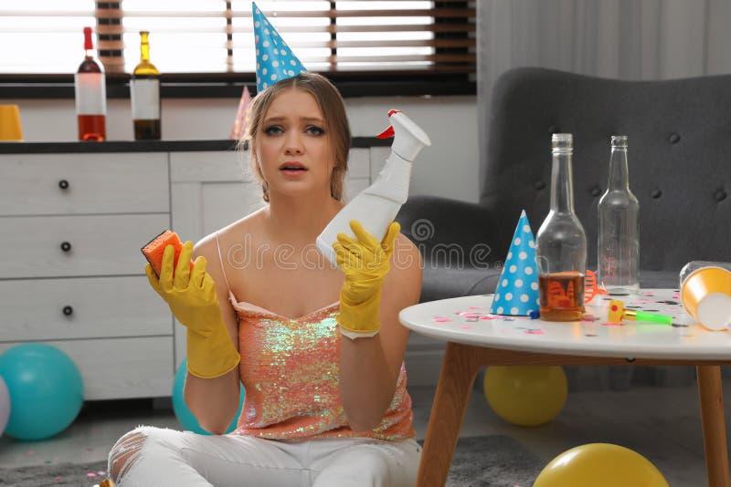 有瓶的疲乏的年轻女人洗涤剂和海绵 库存照片