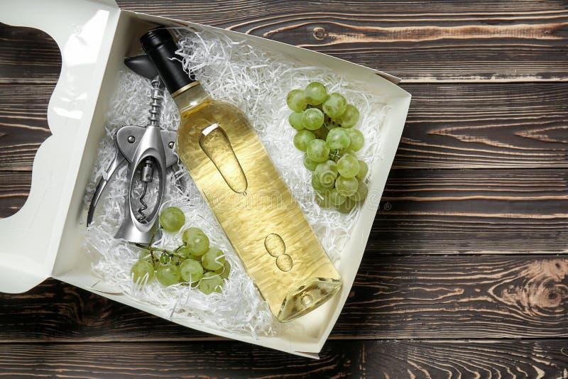 有瓶的纸板箱白酒和拔塞螺旋在木桌上 免版税库存图片